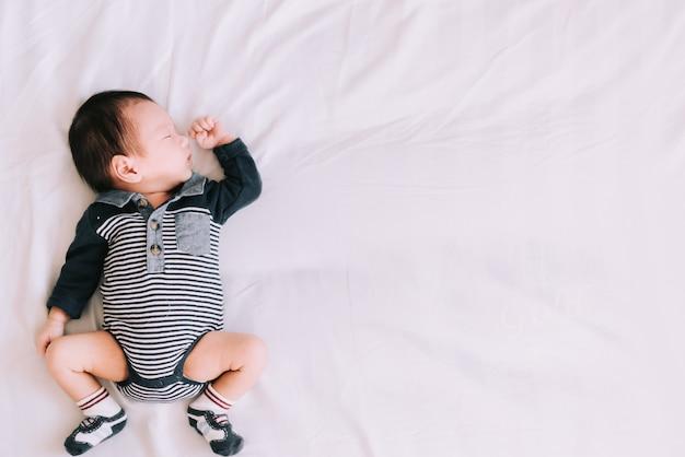Kleines baby, das auf weichem weißem bett im schlafzimmer schläft - glückliche familienmomente