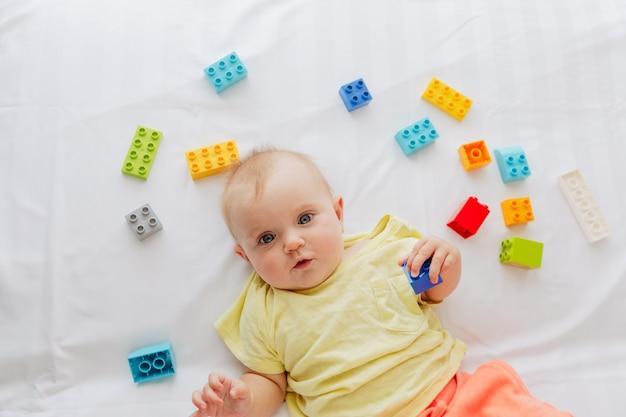 Kleines baby, das auf weißem leinen zwischen spielwaren liegt