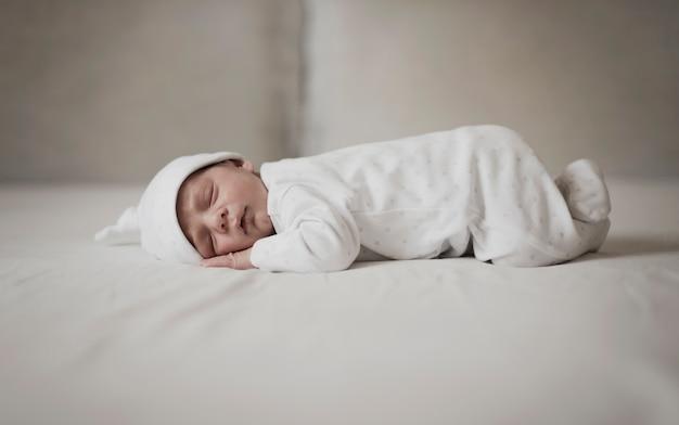 Kleines baby, das auf weißen blättern schläft