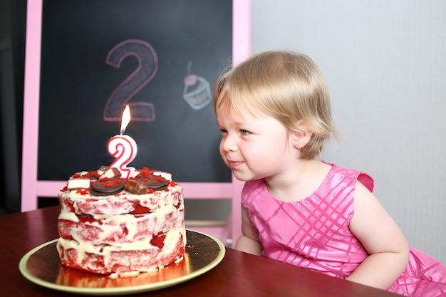 Kleines baby, das eine kerze auf dem kuchen ausbläst. zweijähriger geburtstag