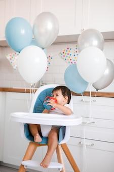 Kleines baby, das im blauen hochstuhl zu hause auf weißer küche und trinkwasser vom trinkbecher sitzt