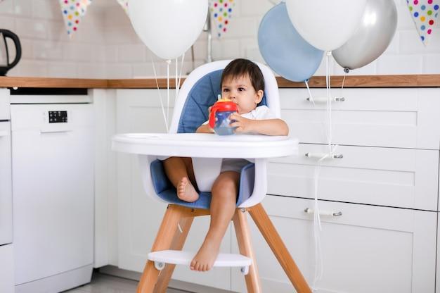 Kleines baby, das im hochstuhl zu hause auf weißer küche und trinkwasser von trinkbecher auf hintergrund mit luftballons sitzt.