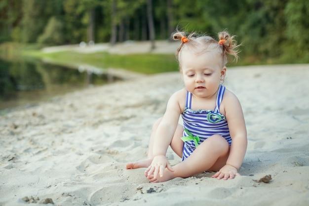 Kleines baby, das im sand spielt.
