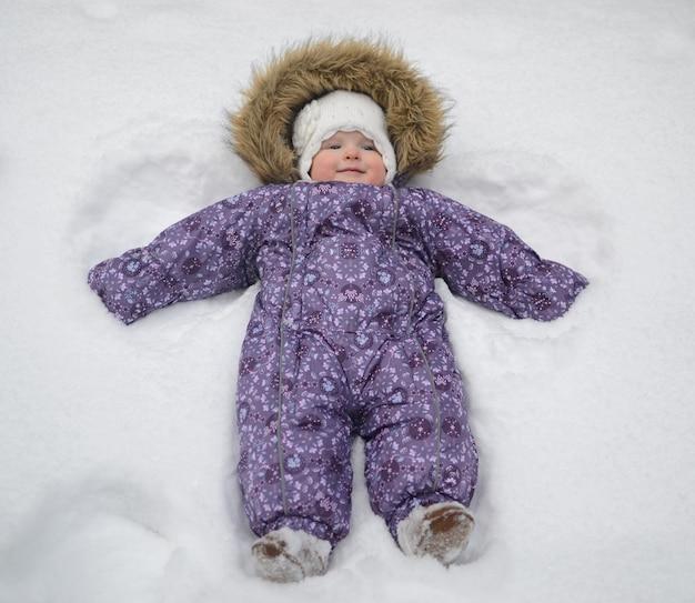 Kleines baby, das im schnee macht einen schneeengel liegt