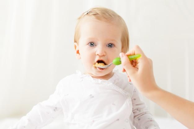 Kleines baby, das mit einem löffel einzieht