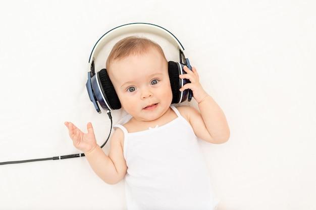 Kleines baby, das mit kopfhörern auf dem bett liegt