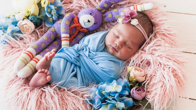Kleines baby, das mit spielzeugfreund schläft