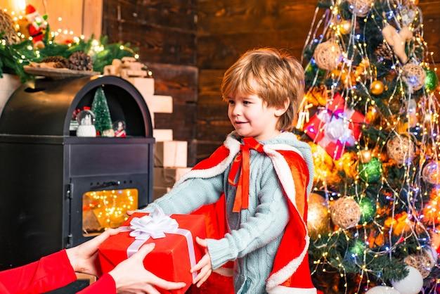 Kleines baby, das neujahrsgeschenk an dekoriertem weihnachtsinnenhintergrund empfängt, schöne chri...