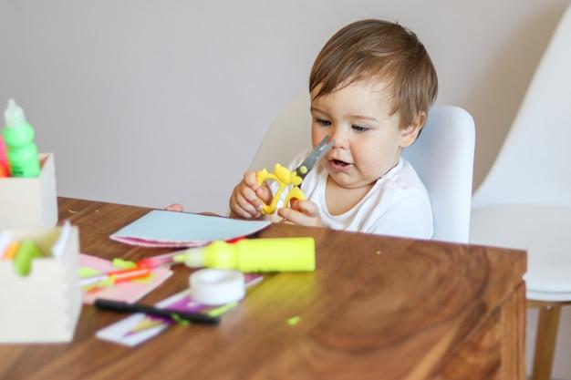 Kleines baby, das scheren in seinen händen hält und büttenpapiergrußkarte macht