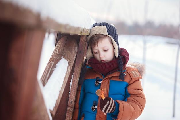 Kleines baby, das süßen jungen hahn am wintertag spielt und isst. kinder spielen im verschneiten wald.