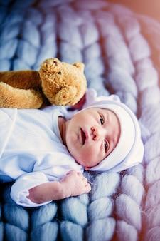 Kleines baby, das weiße kleidung und hut mit taddybären trägt