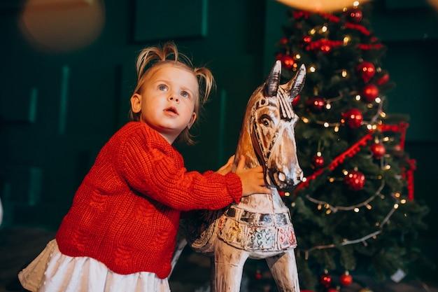 Kleines baby gir; l durch weihnachtsbaum mit hölzernem spielzeug