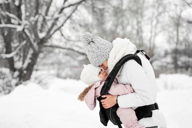 Kleines baby ihre mutter, die draußen in winter geht mutter, die das babybaby tragen hält