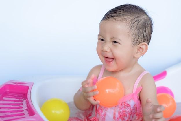 Kleines baby im bad, das ball spielt.