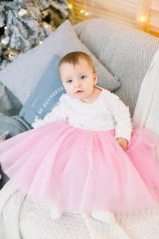 Kleines baby im schönen kleid, sitzend auf sofa, auf dem hintergrund des weihnachtsbaumes.