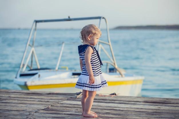 Kleines baby im seemannskleid auf hölzernem pier auf dem hintergrund des bootes
