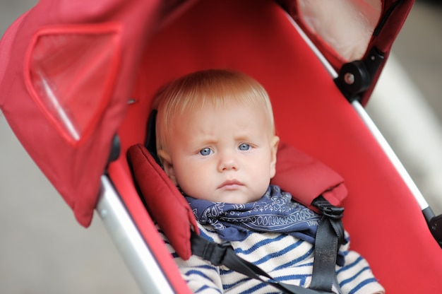 Kleines baby im spaziergänger am frühlingstag