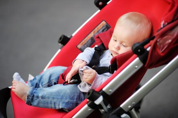 Kleines baby im spaziergänger, der mit seiner socke spielt