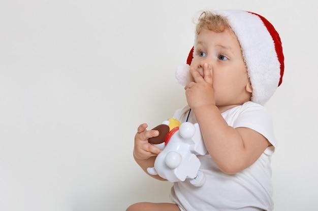 Kleines baby im weihnachtshut, das mit erstaunlichem blick wegschaut, seinen mund mit winzigen fingern bedeckt und plastikhundespielzeug hält