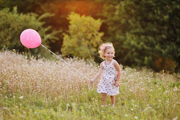 Kleines baby im weißen kleid mit rosa luftballon auf einem hintergrund des grüns, gras bei sonnenuntergang.