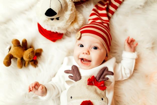 Kleines baby in der strickjacke mit einem rotwild und einem roten hut liegt auf weicher weißer decke