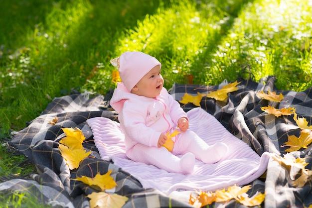 Kleines baby in einem sonnigen herbstpark, der auf einer decke auf dem gras sitzt, das durch verstreute gelbe blätter umgeben ist