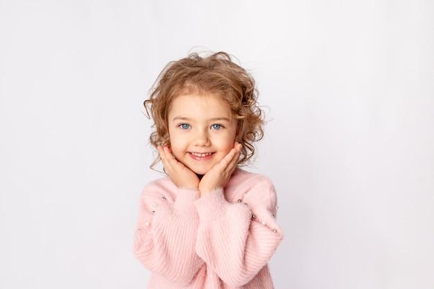 Kleines baby in rosa winterkleidung auf weißem hintergrund freut sich, raum für text