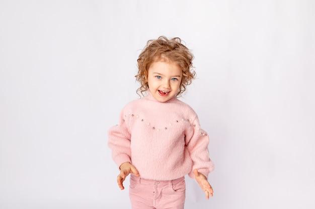 Kleines baby in rosa winterkleidung auf weißem hintergrund