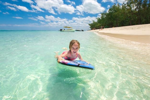 Kleines baby - junger surfer mit bodyboard hat spaß auf kleinen meereswellen. aktiver familienlebensstil