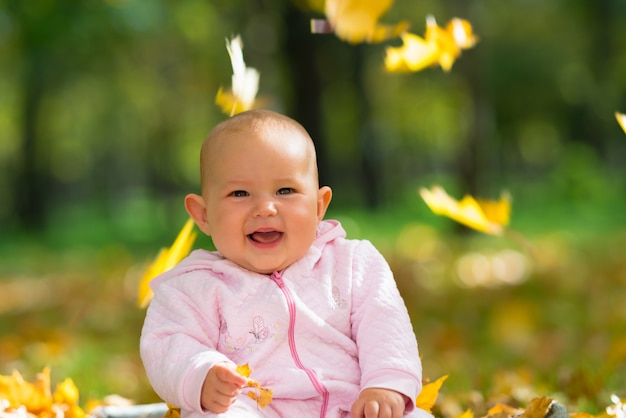 Kleines baby lacht, während sie mit bunten gelben blättern spielt, die von oben in einem herbstpark fallen