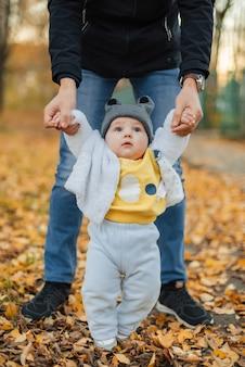 Kleines baby lernt, erste schritte zu unternehmen, die die hände des vatis halten