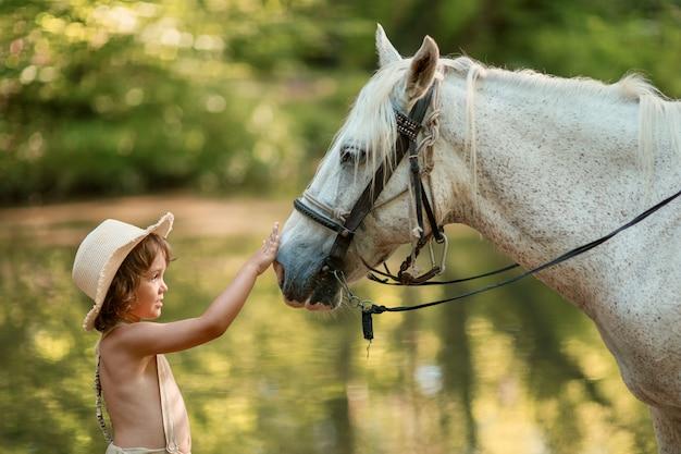 Kleines baby mit dem gelockten haar gekleidet als hobbit, der mit pferd im sommerwald spielt