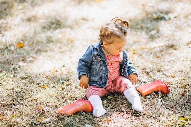 Kleines baby mit den regenstiefeln, die im park sitzen