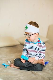 Kleines baby mit down-syndrom mit den großen blauen gläsern, die mit doktorspielwaren spielen