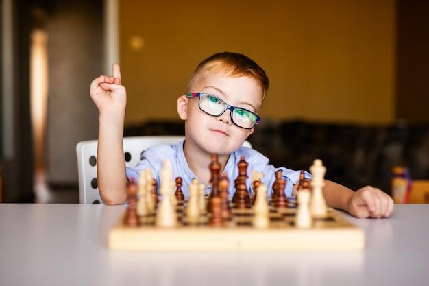 Kleines baby mit down-syndrom mit den großen blauen gläsern, die schach im kindergarten spielen