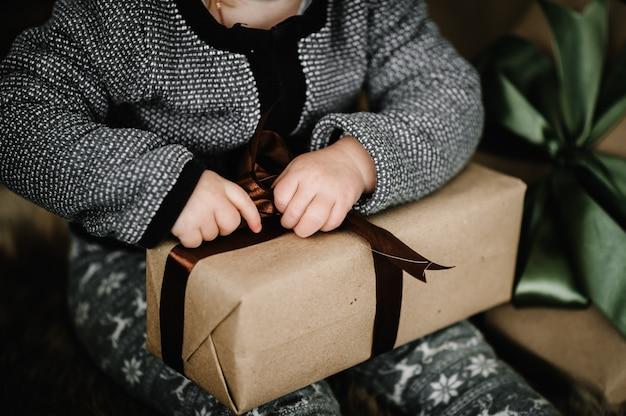 Kleines baby mit einem geschenk, offene geschenke nahe weihnachtsbaum zu hause. das neue jahr 2021, feiertage und kindheitskonzept. nahansicht.