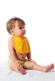 Kleines baby mit lätzchen, das kamera und trinkwasser oder kompott von tasse betrachtet
