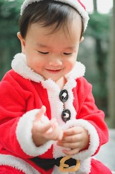Kleines baby mit weihnachtsmann-outfit auf dem boden