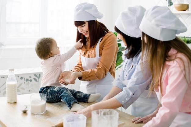 Kleines baby sitzt auf dem holztisch in der küche und hat spaß mit zucker. großmutter und ihre töchter backen kekse. glückliche frauen in weißen schürzen, die zusammen backen. muttertag