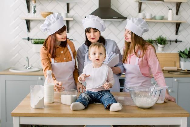 Kleines baby sitzt auf dem holztisch in der küche, während ihre mutter, tante und großmutter das buch mit rezepten auf dem hintergrund lesen. glückliche frauen in weißen schürzen, die zusammen backen