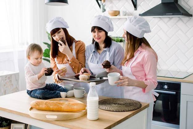 Kleines baby sitzt auf dem tisch in der küche und hat spaß. großmutter und ihre töchter trinken kaffee und essen muffins. glückliche frauen in weißen schürzen, die zusammen backen. muttertag