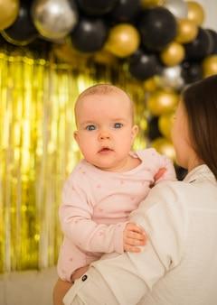 Kleines baby sitzt in den armen ihrer mutter auf goldenen vorhängen