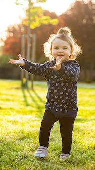 Kleines baby spielt im park in der hintergrundbeleuchtung.