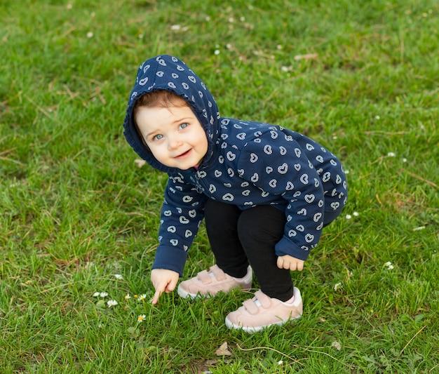 Kleines baby spielt im park und sammelt gänseblümchen