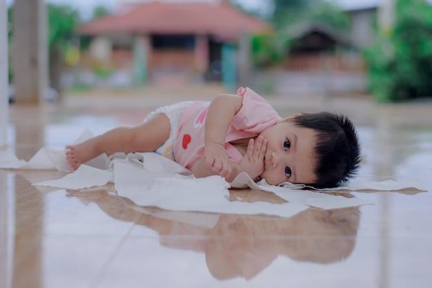 Kleines baby spielt mit toilettenpapier