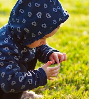 Kleines baby spielt und sammelt gänseblümchen.
