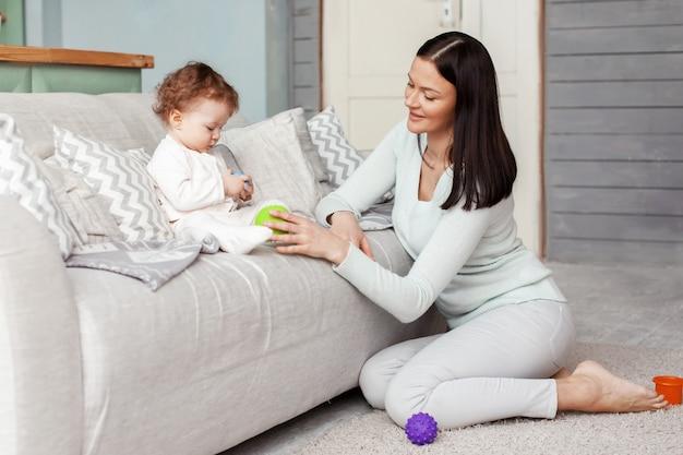 Kleines baby und mutter spielen im zimmer auf der couch mit hellen gummibällen