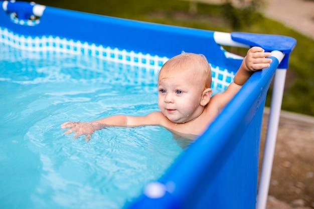 Kleines baby viel spaß mit einem spritzer im schwimmbad.