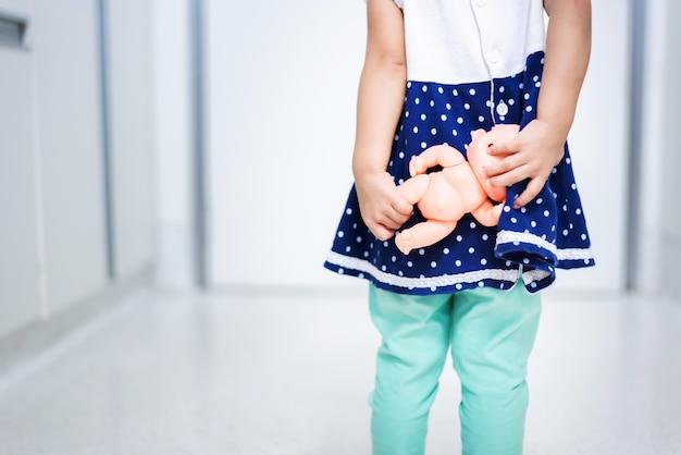 Kleines babykind, das babypuppe ängstlich hält, die tür heraus zu gehen