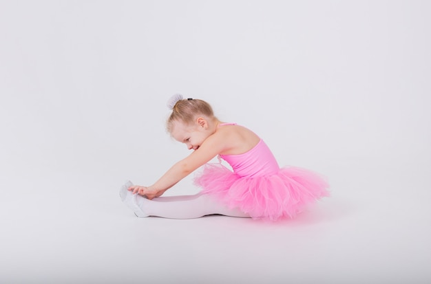Kleines ballerina-mädchen in einem rosa kleid mit einem tutu-rock in weißen spitzenschuhen macht eine strecke auf einer weißen wand